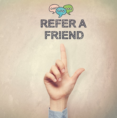 Hand pointing to Refer a Friend concept on light brown wall background Stock Photo