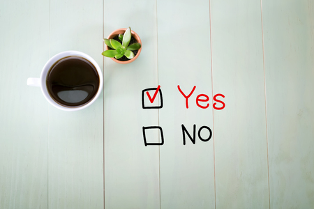 yes no: Yes or No concept with a cup of coffee on a pastel green wooden table