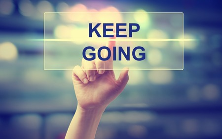 going: Hand pressing Keep Going on blurred cityscape background Stock Photo