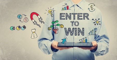 win win: Enter to Win concept with young man holding a tablet computer Stock Photo