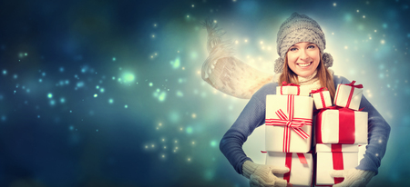cajas navideñas: Mujer joven feliz celebración de muchas cajas presentes en noche de nieve