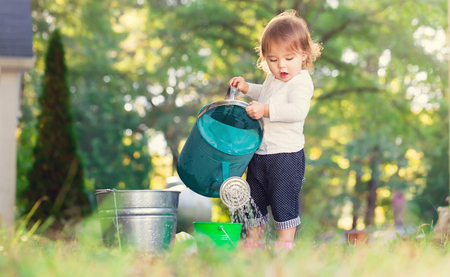 children at play: Happy toddler girl playing with watering cans outside Stock Photo