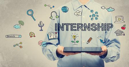 internship: Internship concept with young man holding a tablet computer Stock Photo