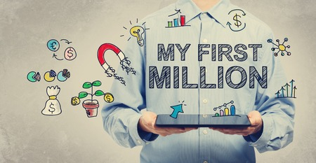 My First Million concept with young man holding a tablet computer Stock Photo
