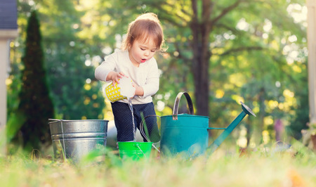 Happy toddler girl playing with watering cans outside Foto de archivo