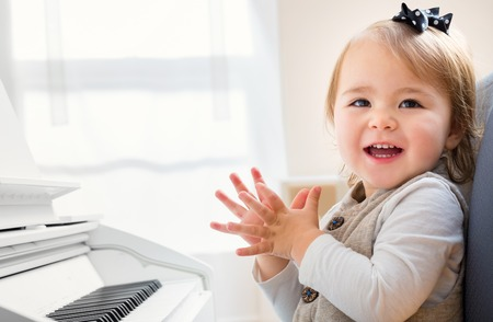 Happy smiling toddler girl excited to play the piano 스톡 콘텐츠