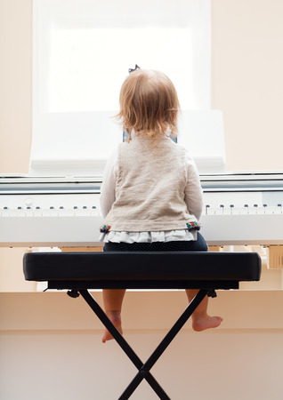 music education: Happy toddler girl playing the piano from behind Stock Photo