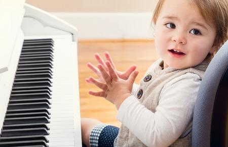 Gelukkig glimlachend peutermeisje opgewonden om piano te spelen