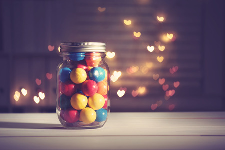 evening glow: Colorful candies in a jar on heart shaped abstract light background Stock Photo