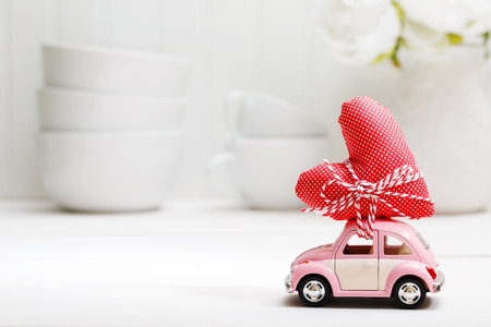 Happy valentines day: Miniature pink car carrying a red heart cushion