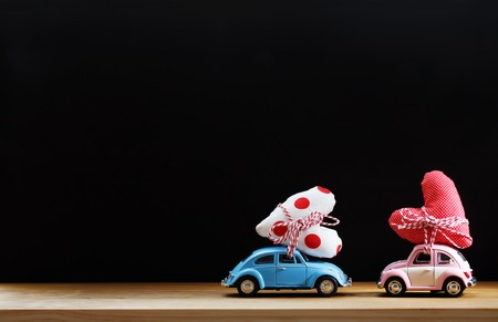 Miniature pink and blue cars carrying heart cushions
