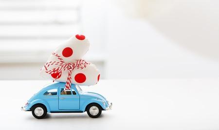 Miniature blue car carrying a polka dots heart cushion
