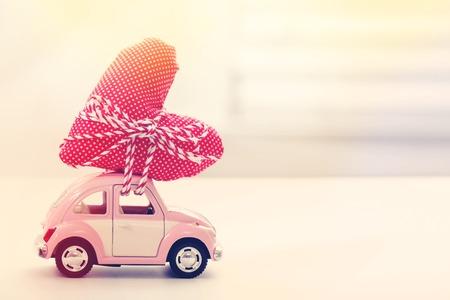estaciones del año: Coche miniatura que lleva un cojín de corazón rojo Foto de archivo
