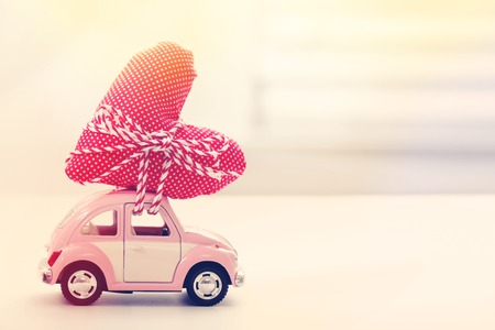 toy car: Miniature car carrying a red heart cushion