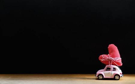 small table: Miniature pink car carrying a red heart cushion