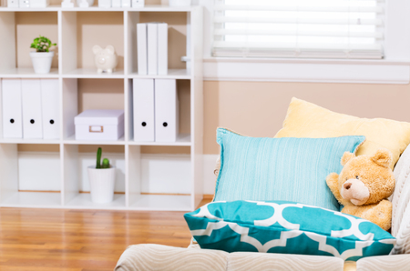 Bright living room interior with a teddy bear and aqua sofa pillows