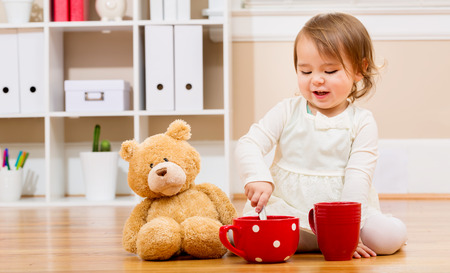 baby playing: Toddler girl having tea time with her teddy bear in her house