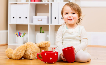 young people party: Toddler girl having tea time with her teddy bear in her house