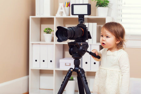 Toddler girl using playing with a professional camera