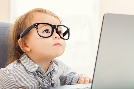 Smart little toddler girl wearing big glasses while using her laptop Banco de Imagens