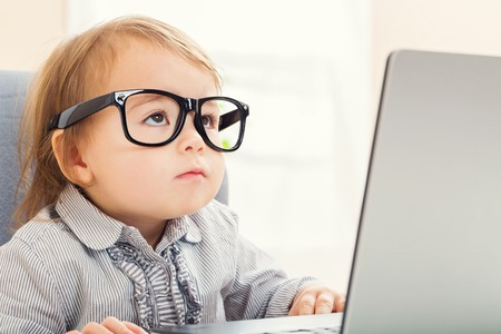 Intelligent toddler girl wearing big glasses while using her laptop