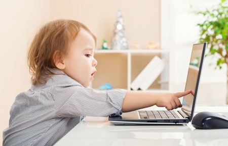 toddler: Little toddler girl  pointing to her laptop computer screen