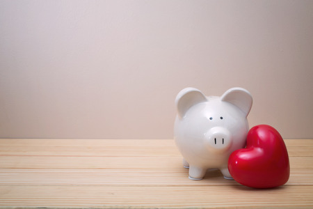 Piggy bank with red heart on a wooden table
