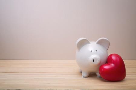 Tirelire avec coeur rouge sur une table en bois