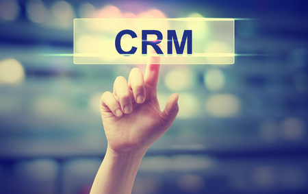 finger shape: CRM - Customer Relationship Management concept with hand pressing a button on blurred abstract background