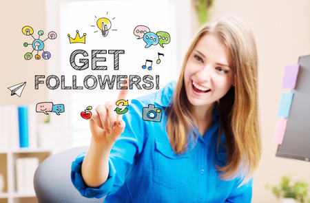 followers: Get More Followers concept with young woman in her home office Stock Photo