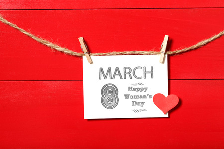 womans: Womans day message card with small red heart hanging with clothespins