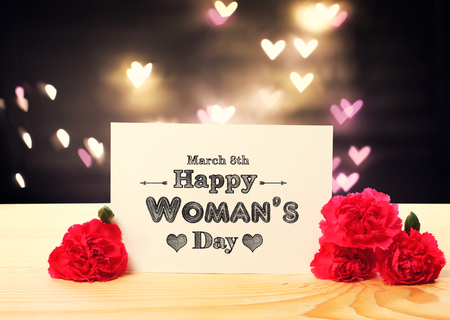 womans: Womans Day message card with carnation flowers and heart shaped lights