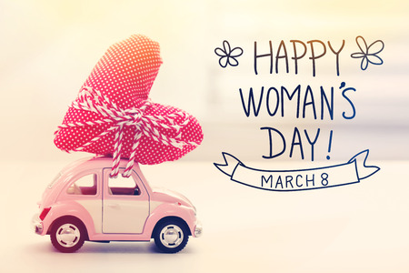 womans: Womans Day message with miniature pink car carrying a heart cushion Stock Photo