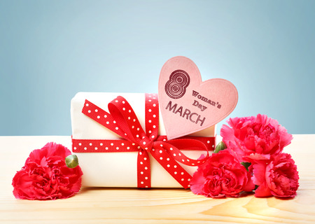 womans: March 8th Womans Day message with present box, flowers and heart shaped tag Stock Photo