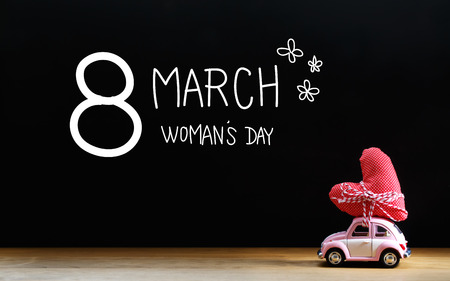womans: Womans Day message with miniature pink car carrying a red heart cushion