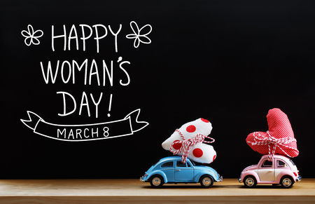 womans: Womans Day message with pink and blue cars carrying heart cushions Stock Photo