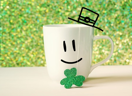 clover face: Saint Patricks Day green clover with happy face on white mug Stock Photo