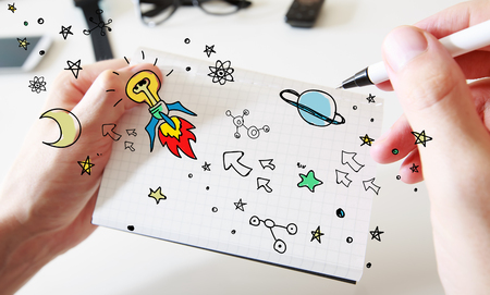 Mans hand drawing Idea rocket concept on white notebook