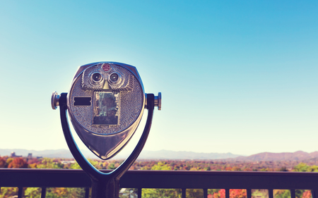 Coin-operated binoculars looking out over an autumn landscape Stock Photo