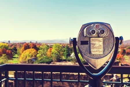 prismáticos que funcionan con monedas que mira hacia fuera sobre un paisaje de otoño Foto de archivo
