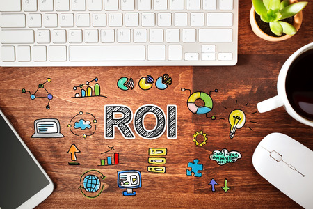 workstation: ROI concept with workstation on a wooden desk Stock Photo