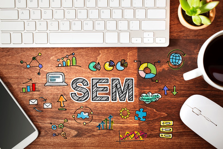 SEM - Search Engine Marketing concept with workstation on a wooden desk