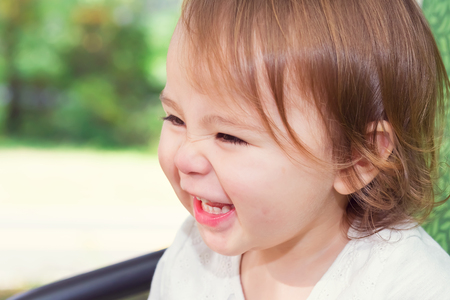 Happy toddler girl laughing while playing on a swing outside Banco de Imagens