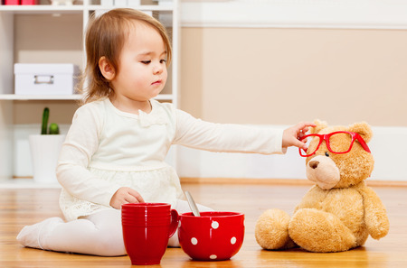 play room: Toddler girl having tea time with her teddy bear in her house
