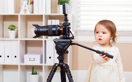 camera girl: Toddler girl using playing with a professional camera