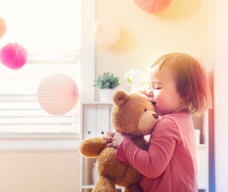 家で彼女のテディベアと遊んで幸せな幼児の女の子