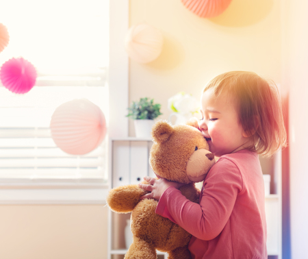 plaything: Happy toddler girl playing with her teddy bear at house