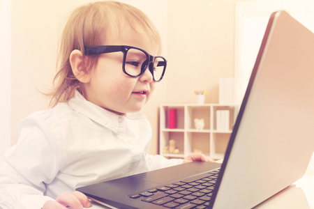 viewing: Smart little toddler girl wearing big glasses while using her laptop Stock Photo