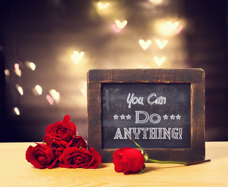 anything: You can do anything message on a small chalkboard with red roses