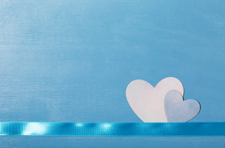 symbolics: Hand cut hearts and ribbon on blue wood texture background
